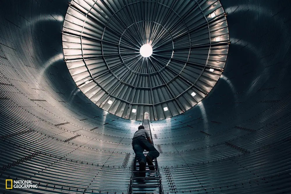 A man climbs to dizzying heights, up a large bin that is soon to be filled with grain in New Raymer, Colorado.