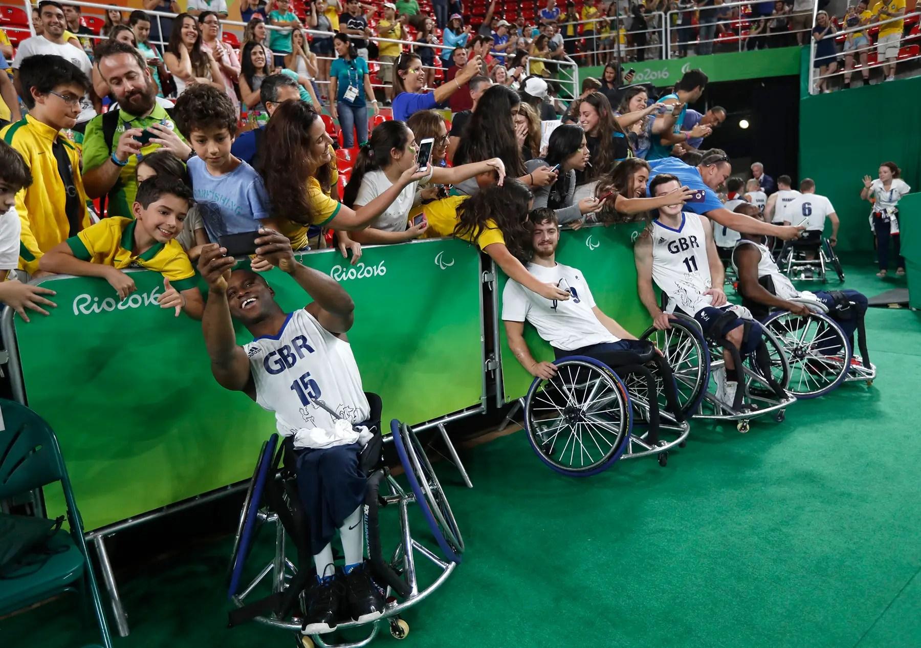 Los miembros del equipo de baloncesto en silla de ruedas de los hombres del equipo de Gran Bretaña posan para selfies después de un partido.