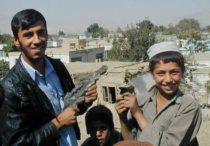 Mohammed Anwar, left, and an unidentified boy in Kabul, Afghanistan, display pieces of shrapnel from bombs dropped Monday morning, October 8, 2001.