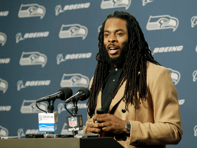 Richard Sherman gives a press conference in a tan suit