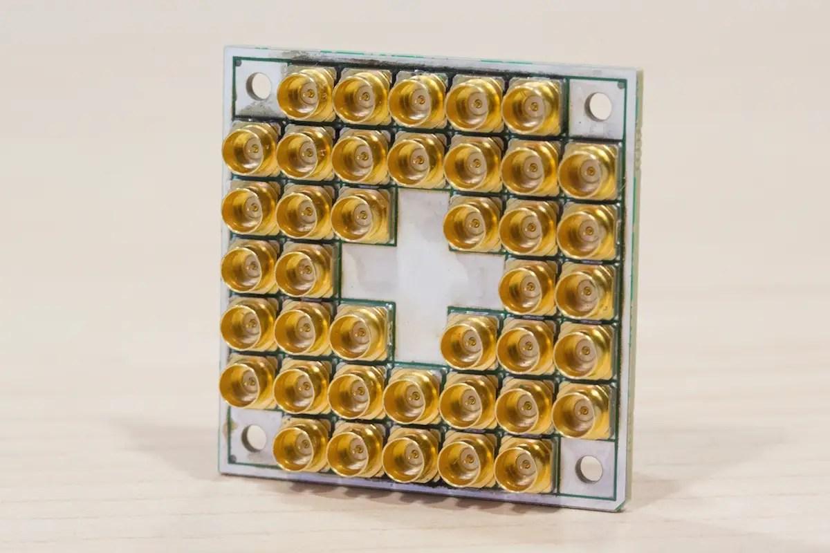 O chip de teste 7-qubit da Intel é de cerca de um quarto. Os conectores de ouro permitem que o chip seja conectado ao mundo fora do computador quântico.