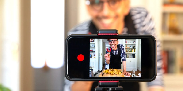 youtuber recording smartphone video of cooking