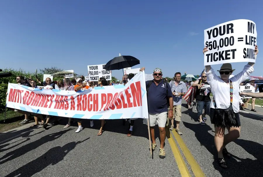 """Playing off of the pronunciation of Koch's name, protesters marched with a banner declaring """"Mitt Romney has a Koch problem."""""""