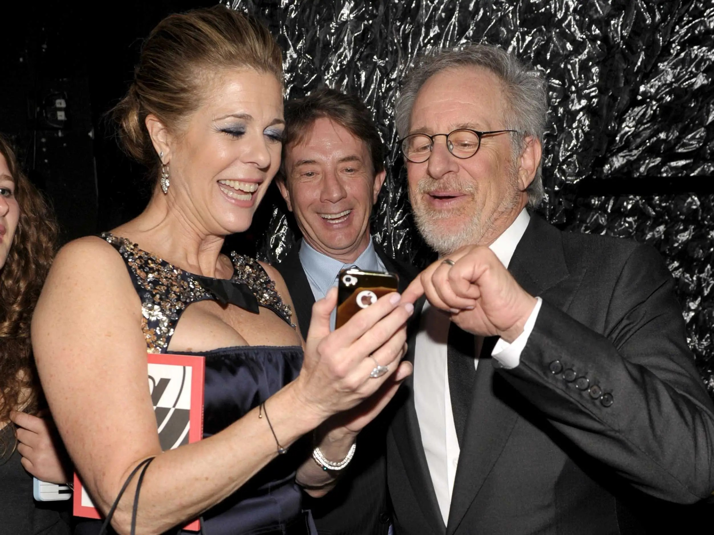 April 2012: Rita Wilson, Martin Short, and Steven Spielberg all look at Wilson's customized gold iPhone at a fundraiser in Beverly Hills.