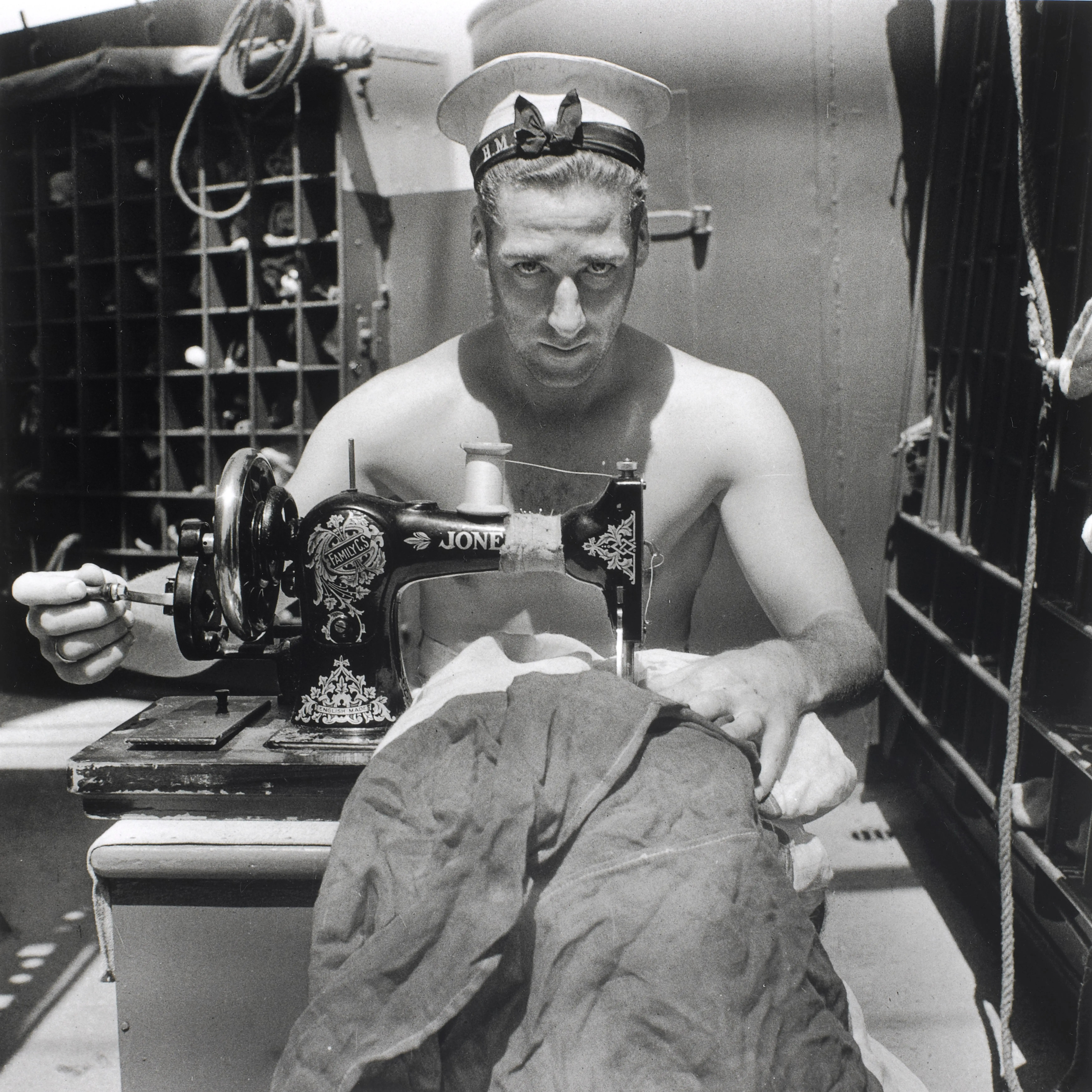 A Royal Navy sailor on board HMS Alcantara uses a portable sewing machine to repair a signal flag during a voyage to Sierra Leone