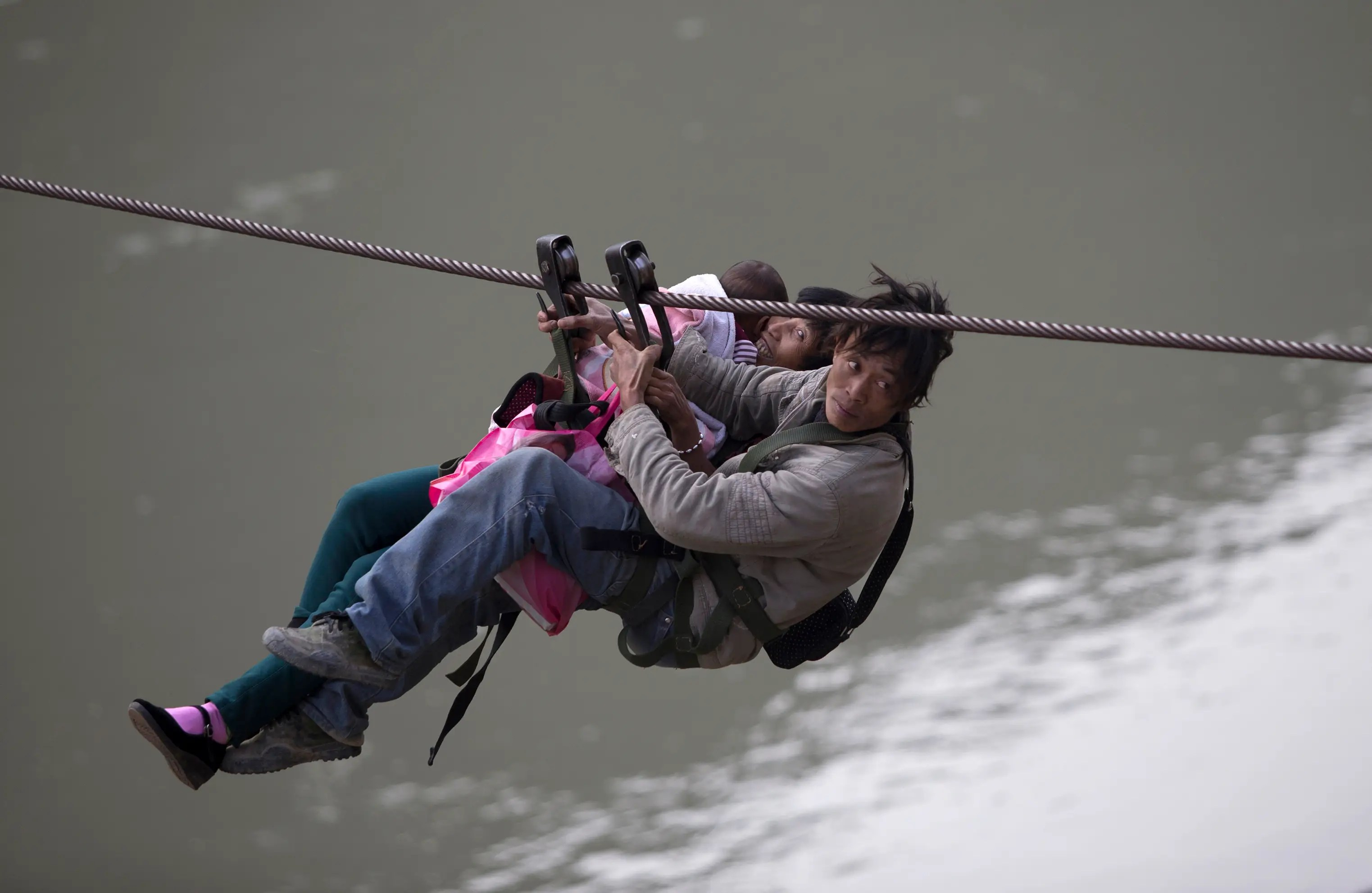 A man, his wife and their child use a zip-line to cross the Nujiang River in Lazimi village of Nujiang Lisu Autonomous Prefecture. Residents have been using the zip-line for years to cross the river as there is no bridge nearby, local media has reported.