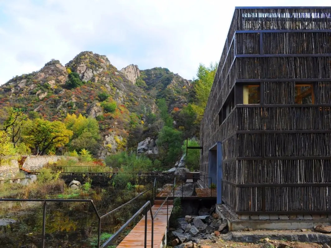 Taking a cue from its forest surroundings in a small town in Beijing, China, the exterior of the Liyuan Library is covered in sticks, and the interior is composed of timber beams. This eco-friendly library is cooled by the lake that it sits on.
