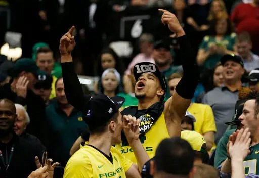 Oregon forward Dillon Brooks celebrates with fans after his team defeated Utah in an NCAA college basketball game in the championship of the Pac-12 men's tournament Saturday, March 12, 2016, in Las Vegas. Oregon won 88-57. (AP Photo/John Locher)
