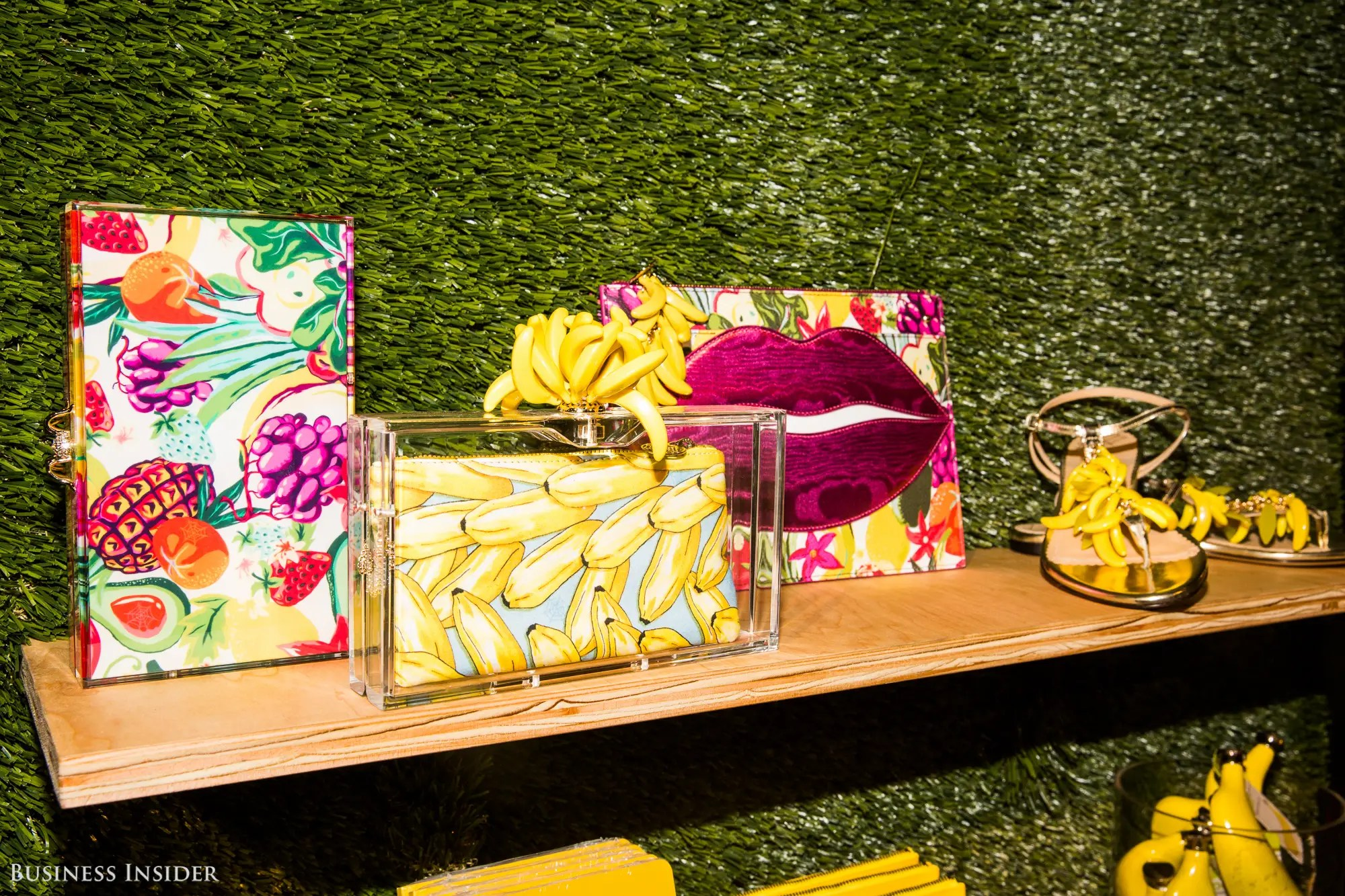 The banana-themed clutch and sandals pictured below cost $1,095 and $795 respectively. They're surrounded by other banana-themed items, like flasks and notebooks.