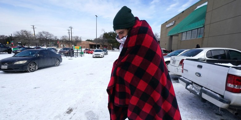 Cody Jennings uses a blanket to keep warm outside a grocery store Tuesday, Feb. 16, 2021, in Dallas.