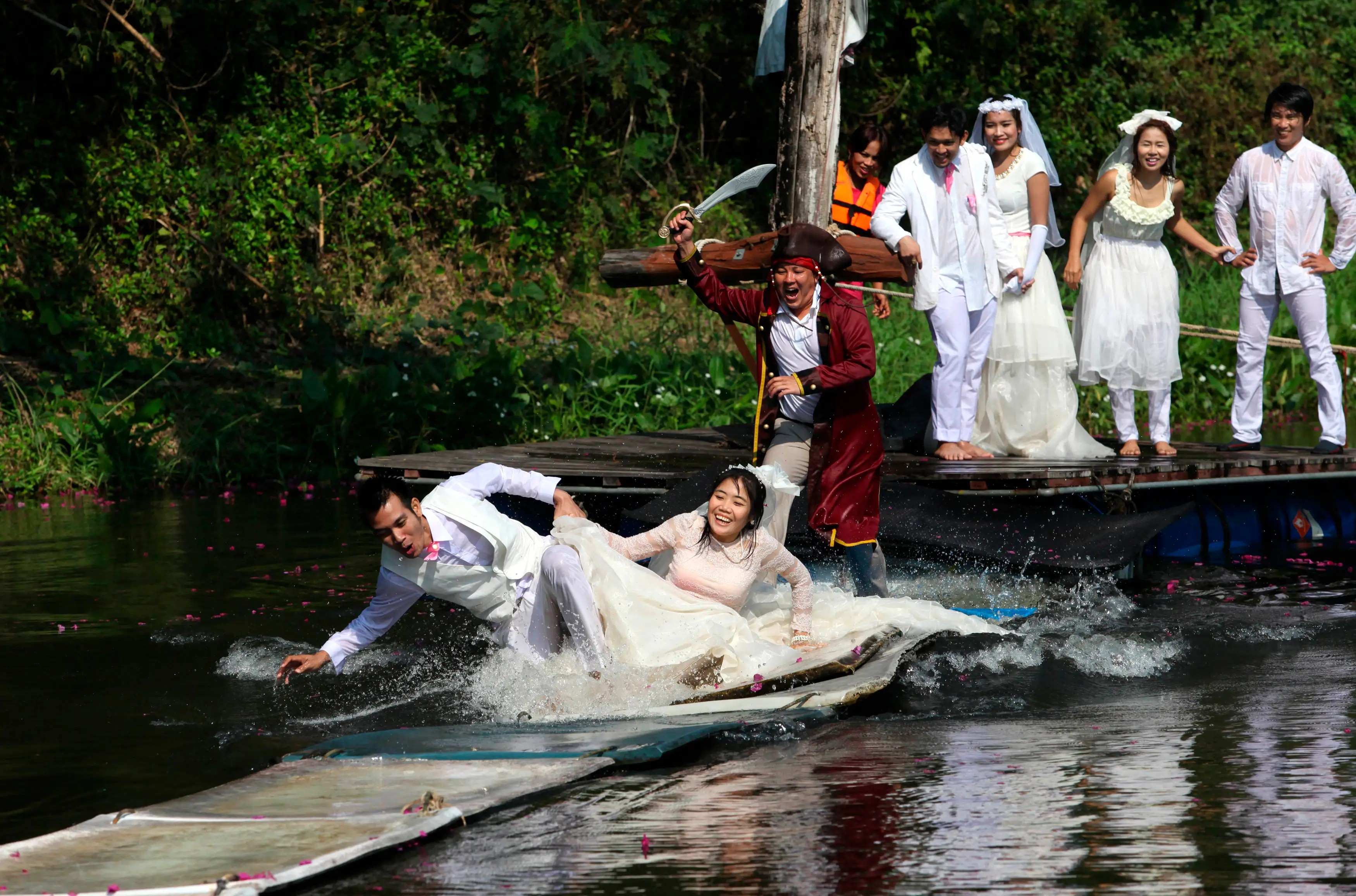 Sorawich Changtor and his bride Rungnapa Panla run to escape a man dressed as a pirate in Prachin Buri province, east of Bangkok, Thailand.