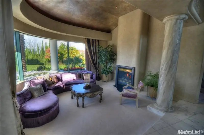 Lounge on another purple couch in this comfortable sitting area, complete with fireplace.