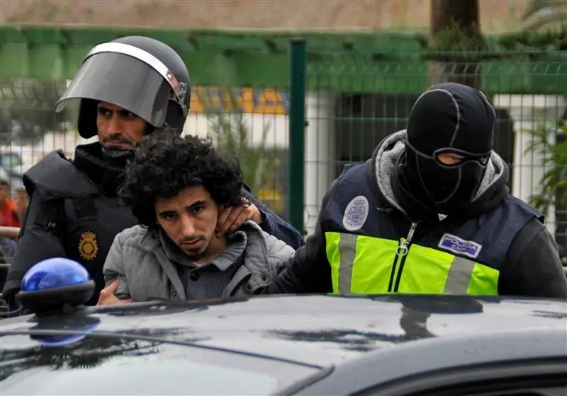 Masked Spanish National Police officers detain a man suspected to be a member of an Islamist militant cell in Melilla March 14, 2014. REUTERS/Jesus Blasco de Avellaneda