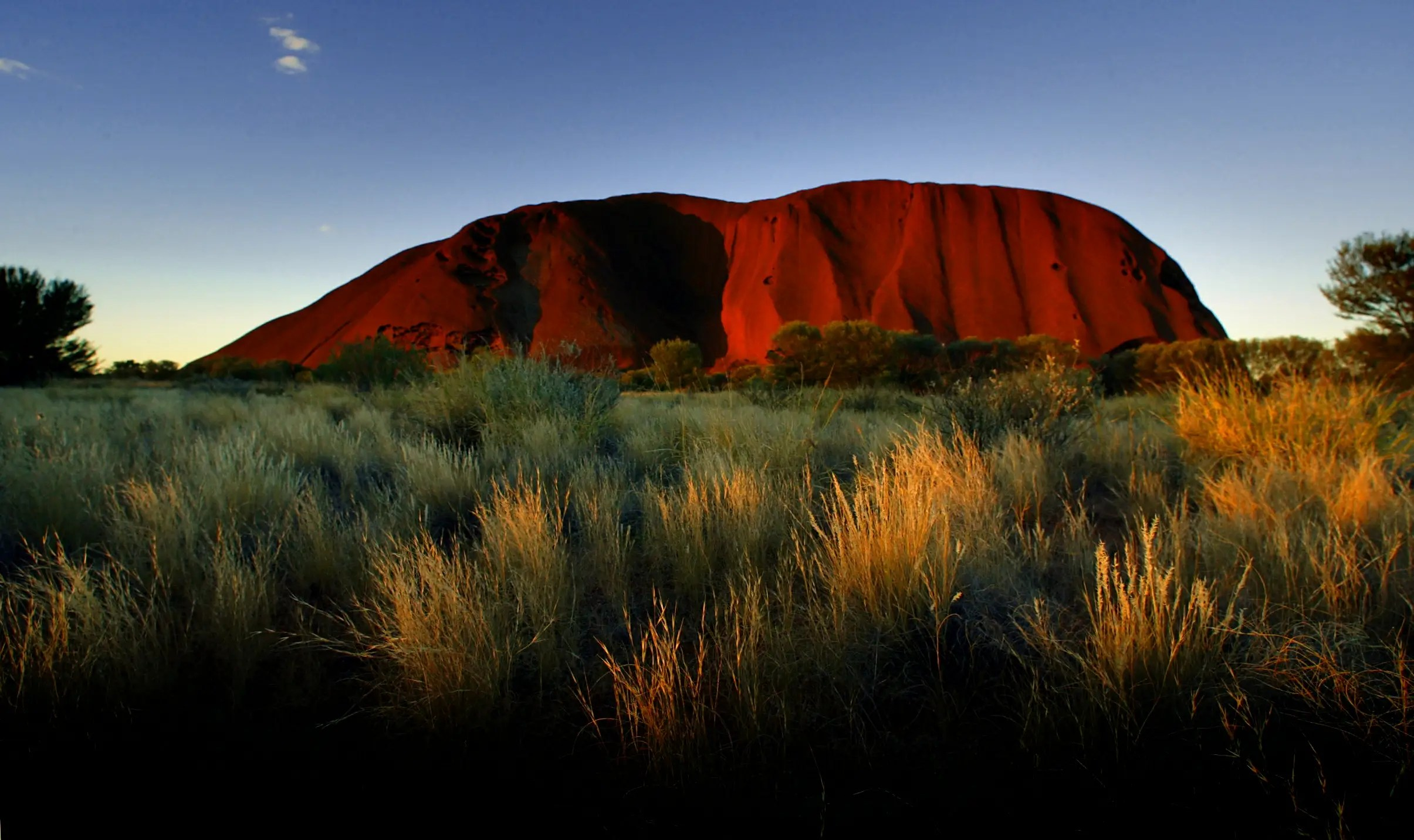The sun sets on Ayers Rock, one of Australia's major tourist destinations, attracting 400,000 visitors every year.