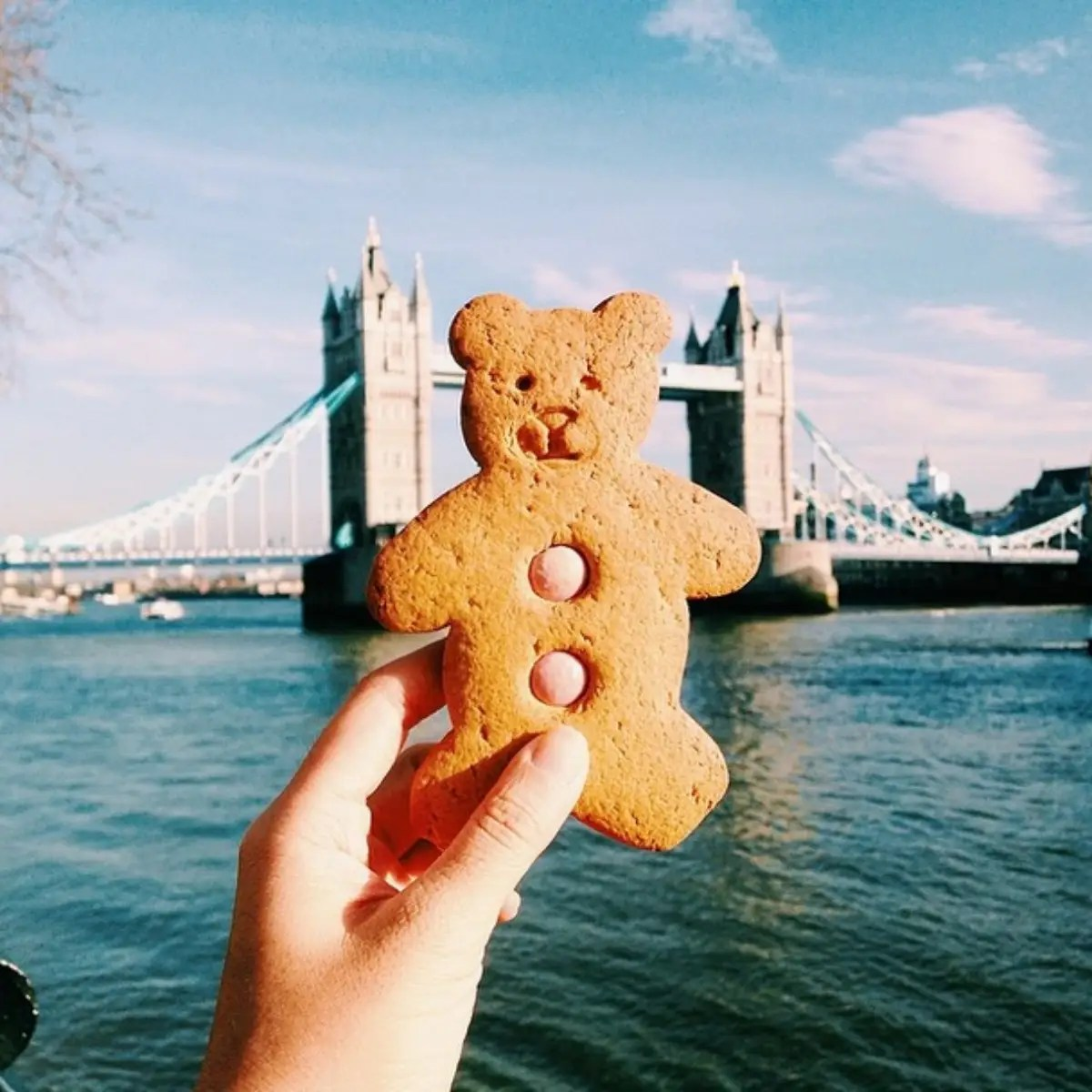 Tower Bridge in London, enjoying a cute teddy bear cookie I got from Borough Market.