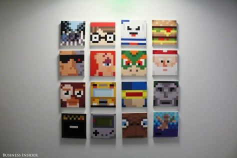 "At the end of the hall, a gallery wall displays works of ""bit art,"" or illustrations using large pixels of solid color to make recognizable figures. Marvel's Cyclops, Nintendo's Bowser, a Game Boy, E.T., Santa Claus, and others appear."