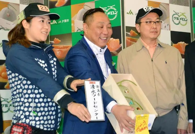 A successful bidder (C) shows a single pair of Yubari melons with a price of 1.5 million yen (,400) after this year's first auction at the Sapporo Central Wholesale Market on Hokkaido island on May 22, 2015