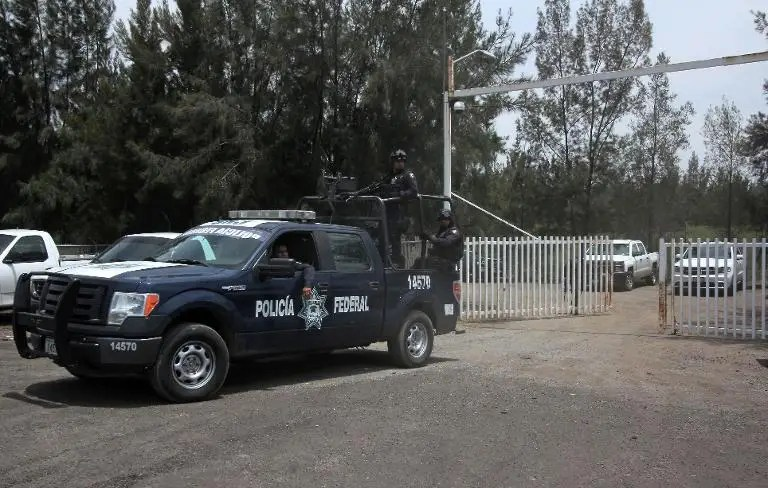 Members of the Federal police leave a ranch along the Jalisco-Michoacan highway in Vista Hermosa, Michoacan State, on May 22, 2015 where gunmen took cover during an intense gun battle with the police