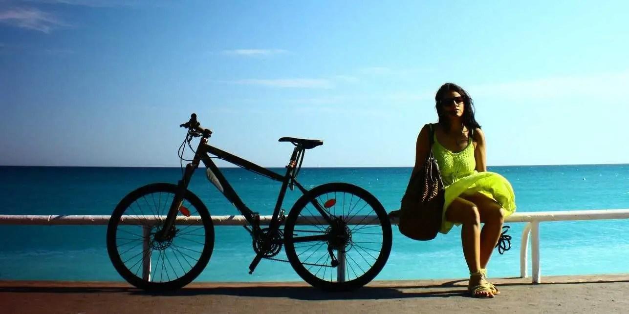woman with bike on beach