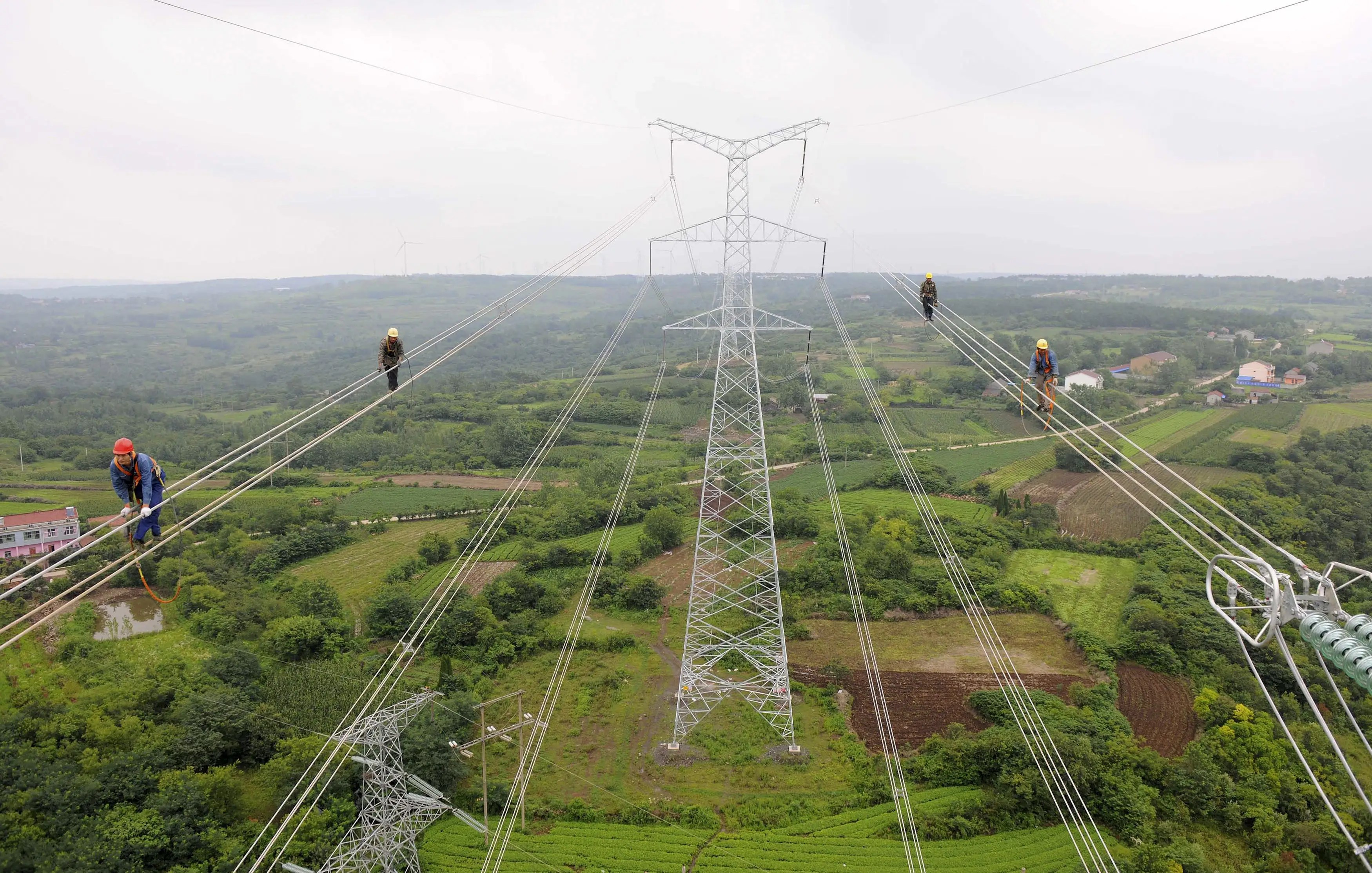 Workers walk along wires as they inspect newly-built electricity pylons above crop fields in Chuzhou within the Anhui province of China.