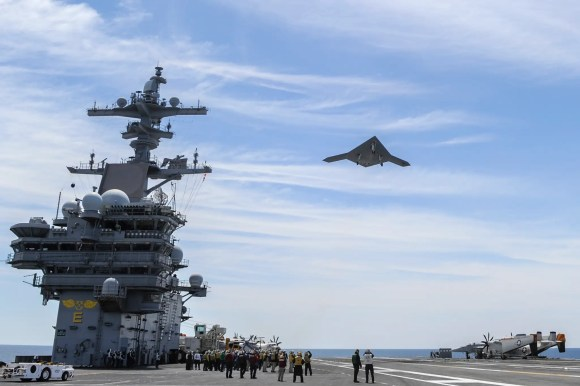 A Northrop Grumman X-47B Unmanned Combat Air System demonstrator flies over the aircraft carrier USS George H.W. Bush after successfully completing a catapult launch.