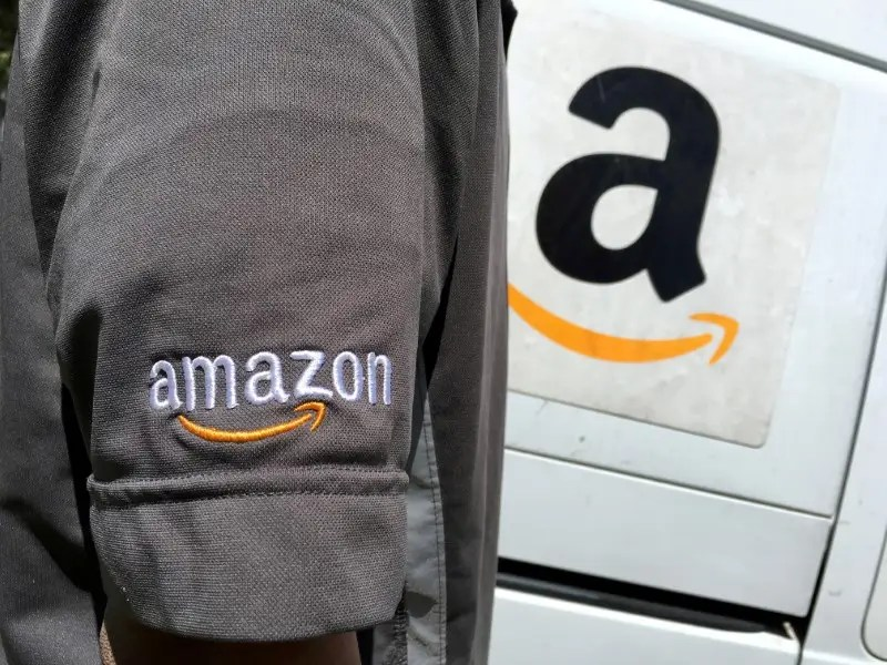 FILE PHOTO: An Amazon.com Inc driver stands next to an Amazon delivery truck in Los Angeles, California, U.S. on May 21, 2016. REUTERS/Lucy Nicholson/File Photo - RC117144E570