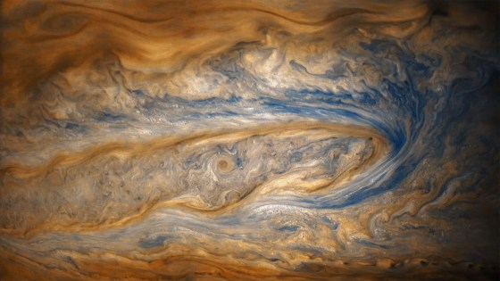In this older view of Jupiter, from Juno's eighth perijove, two cloud bands battle for dominance — one of which contains a swirling storm many times larger than a hurricane on Earth.