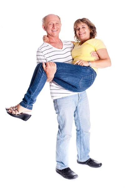 Playful senior couple having fun indoors - Stock Photo