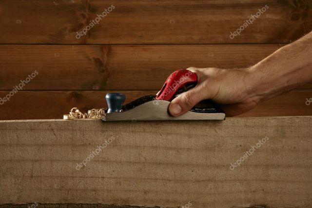 Carpenter planning wood planer tool man hand wooden background