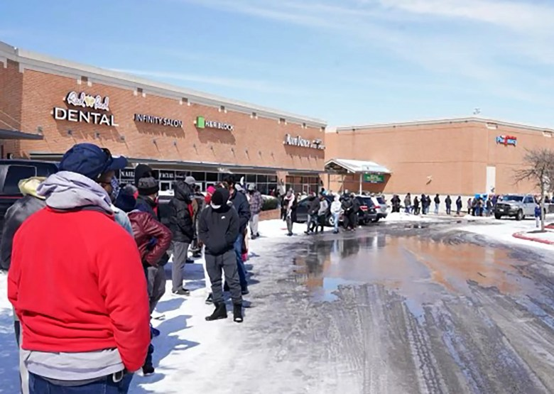 People wait in line at a mall to get inside an H-E-B supermarket in Round Rock, Texas, on February 16, 2021