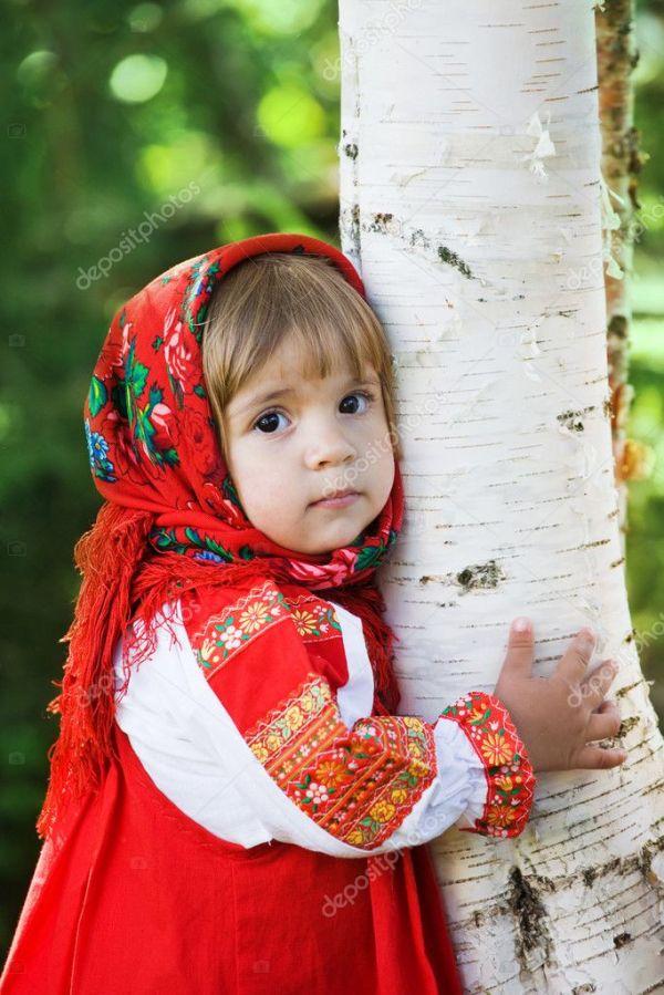 Маленькая девочка в умном сарафане обнимает березу ...