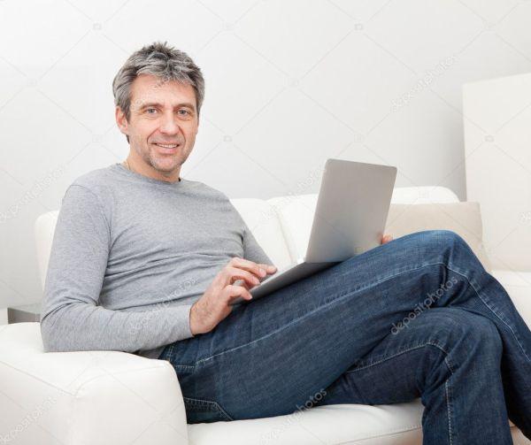 Старший мужчина сидит в диван и с помощью ноутбука ...