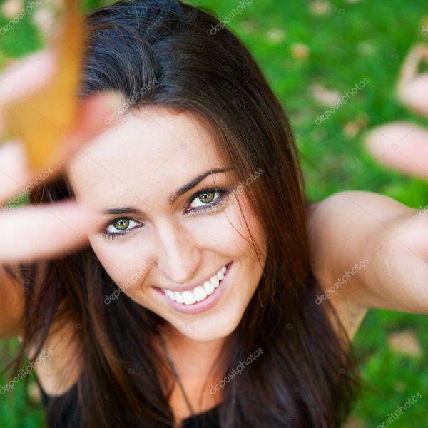 Портрет улыбающийся молодой девушки, сидя на траве в лесу ...