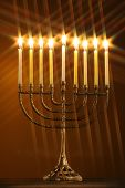 image of menorah - different perspective on a traditional hanukah menorah with all candle lite with star filter on a gold background - JPG