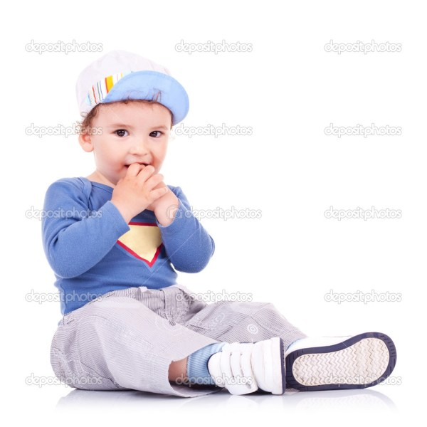 Lovely kid sitting and holding his hands in his mouth ...