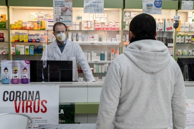 Farmacéutico con mascarilla atendiendo a un usuario. / J. L. Pindado.