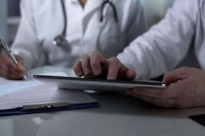 Médico consultando a una compañera una prueba.