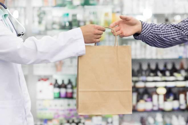 Farmacéutico entrega compra a un cliente
