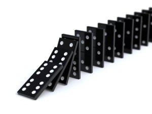 photograph of dominoes falling to illustrate causation.