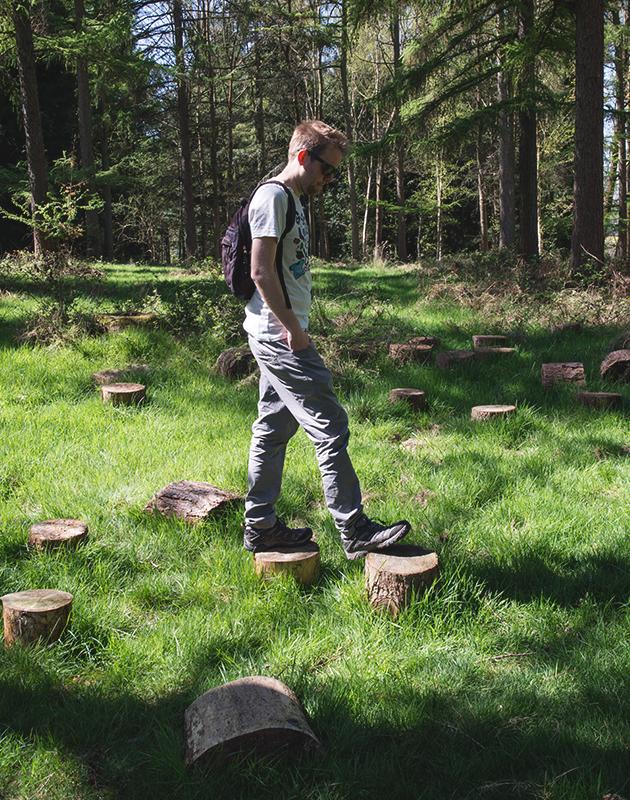 Man stepping on tree stumps