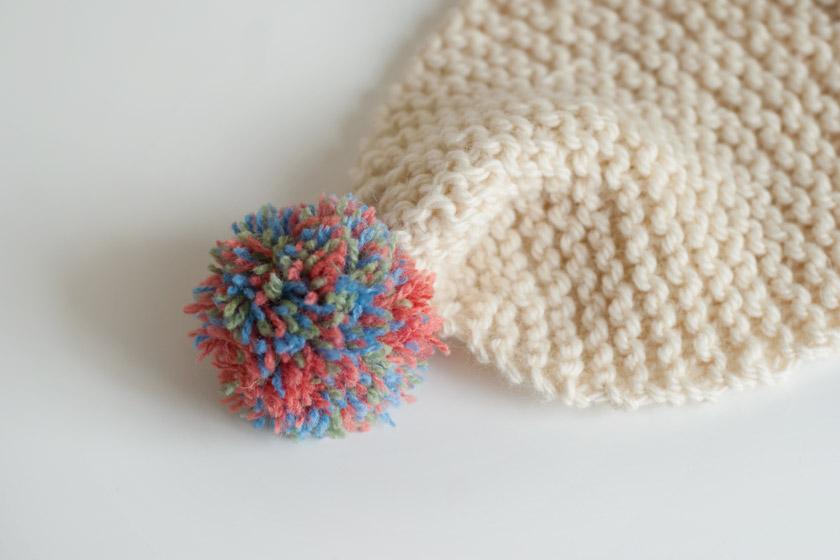 Multicoloured pompom on scarf