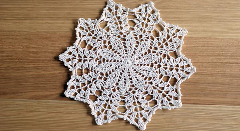 Crochet doily on wooden table