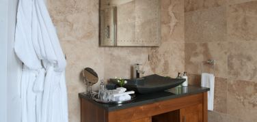 Tiled walled bathroom with black slate sink unit and fluffy white bath robes hanging from the door