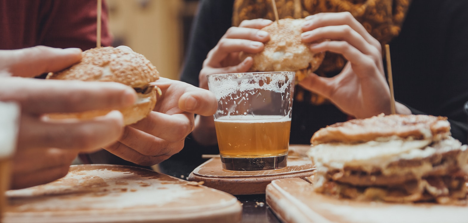 People holding burgers served on wooden chopping boards with a glass of beer in the centre