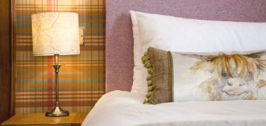 Bed pillow with white linen, pink headboard and a lamp with a map of Grantown on Spey on the shade alongside a Highland cow cushion