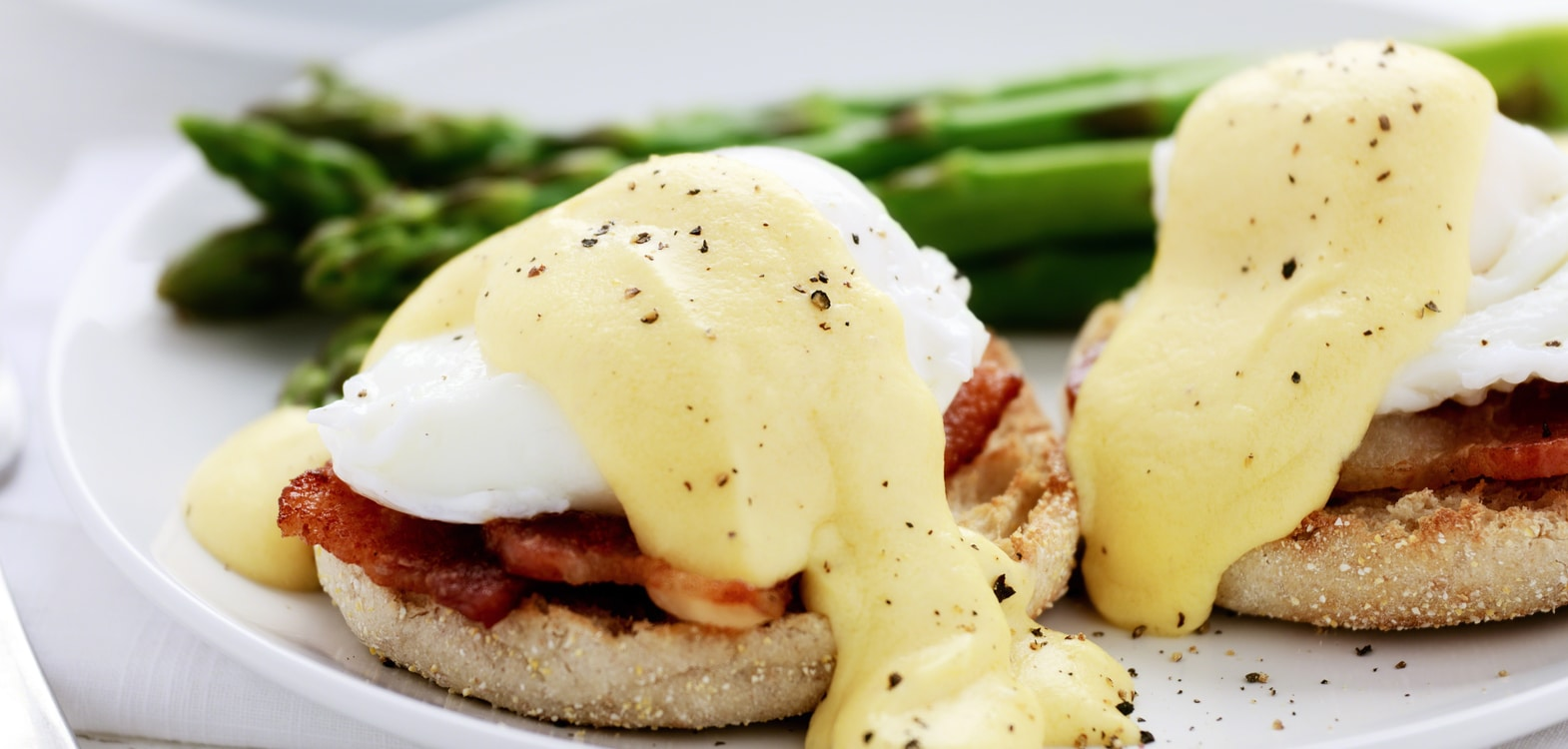 English muffins topped with grilled bacon, poached eggs and hollandaise sauce with black pepper with asparagus in the background