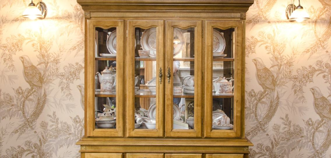 Glass fronted storage cabinet filled with antique crockery and tablewear standing against wall decorated with intricate wallpaper depicting pheasants