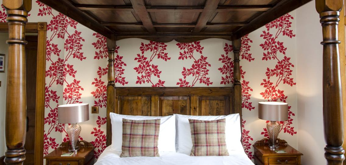 Oak four poster bed in the Rowan Room at Strathallan Guest House with tartan cushions and red patterned wallpaper