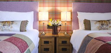 twin beds in Stag bedroom at Strathallan Guest House with Highland cow cushions and large pastel patchwork throws
