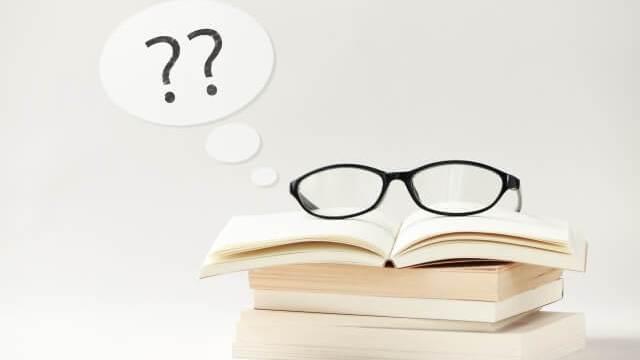 本の上にメガネと?マーク